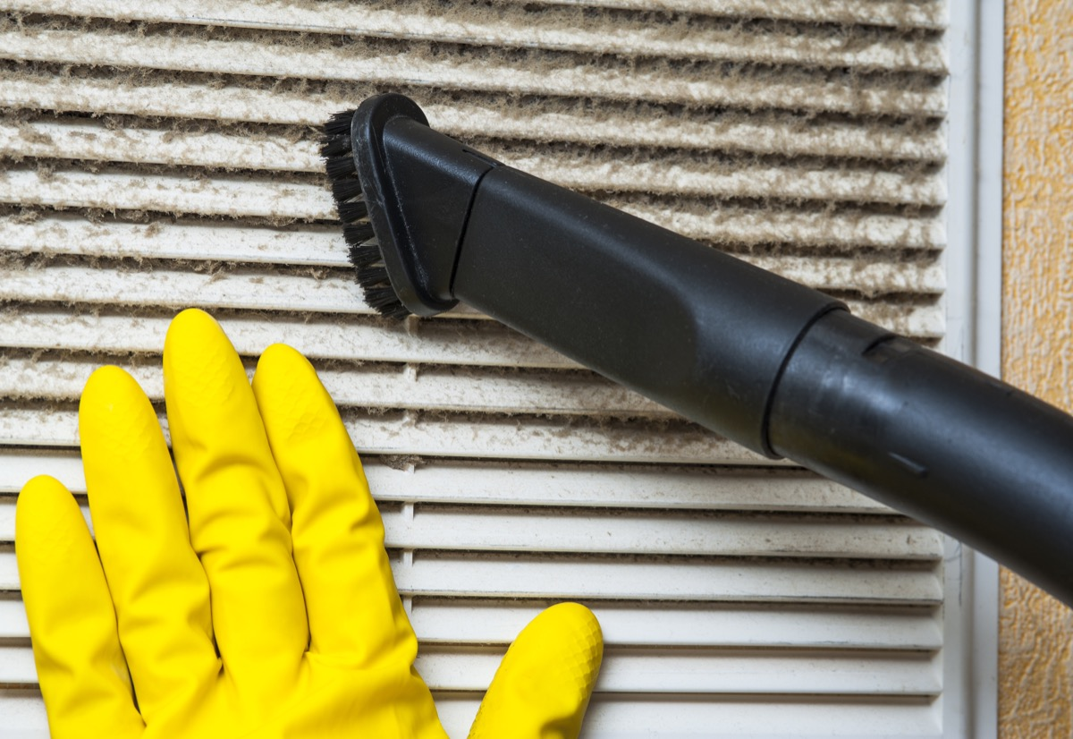 Hand in yellow glove and vacuum cleaner pipe. Ventilation grill cleaning