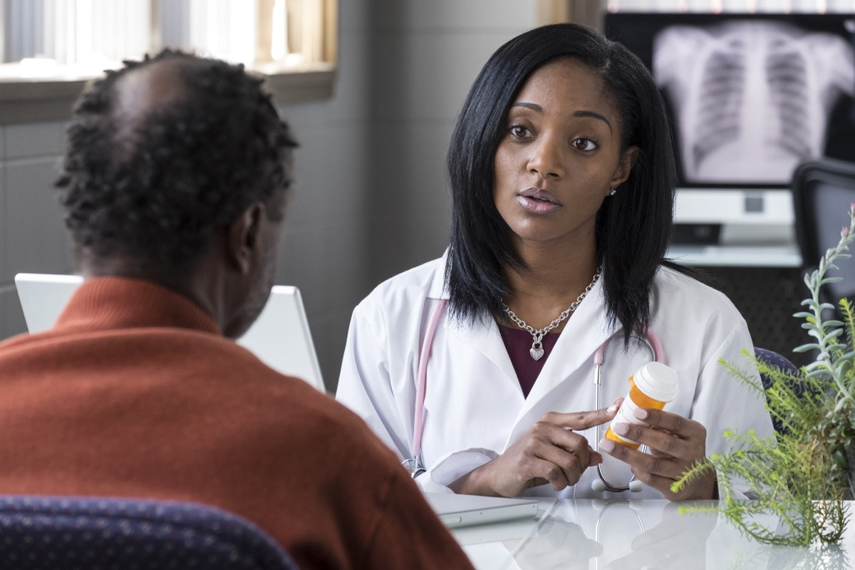 female physician prescribing pills to an older black male patient