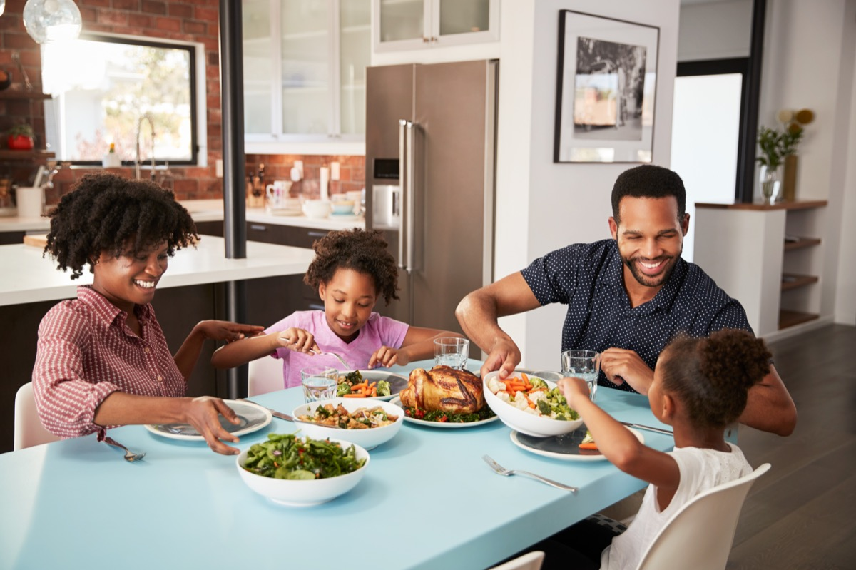 Family Enjoying Meal Around Table At Home Together