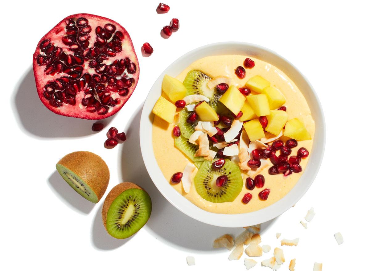golden mango smoothie bowl with pomegranate and kiwi