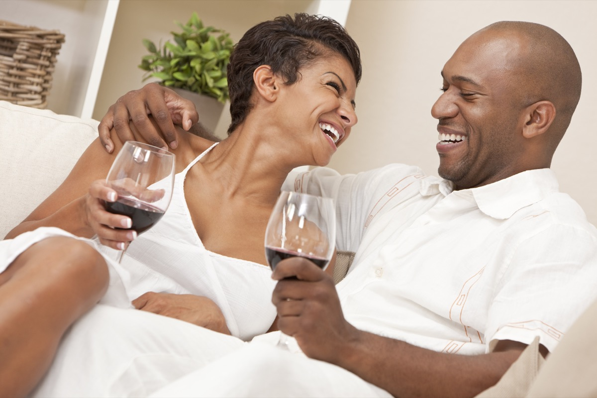 couple sitting at home together laughing and drinking glasses of red wine