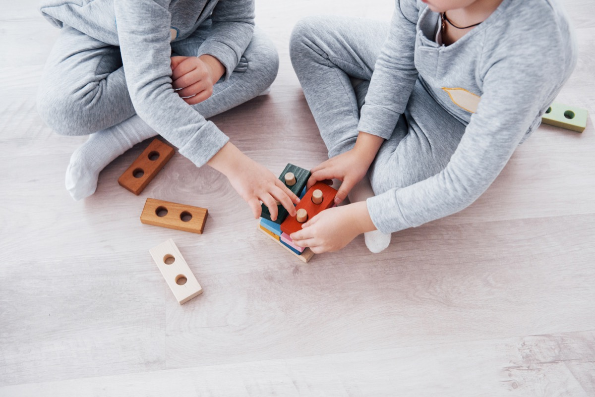 Children play with a toy designer on the floor of the children's room. Two kids playing with colorful blocks. Kindergarten educational games. - Image