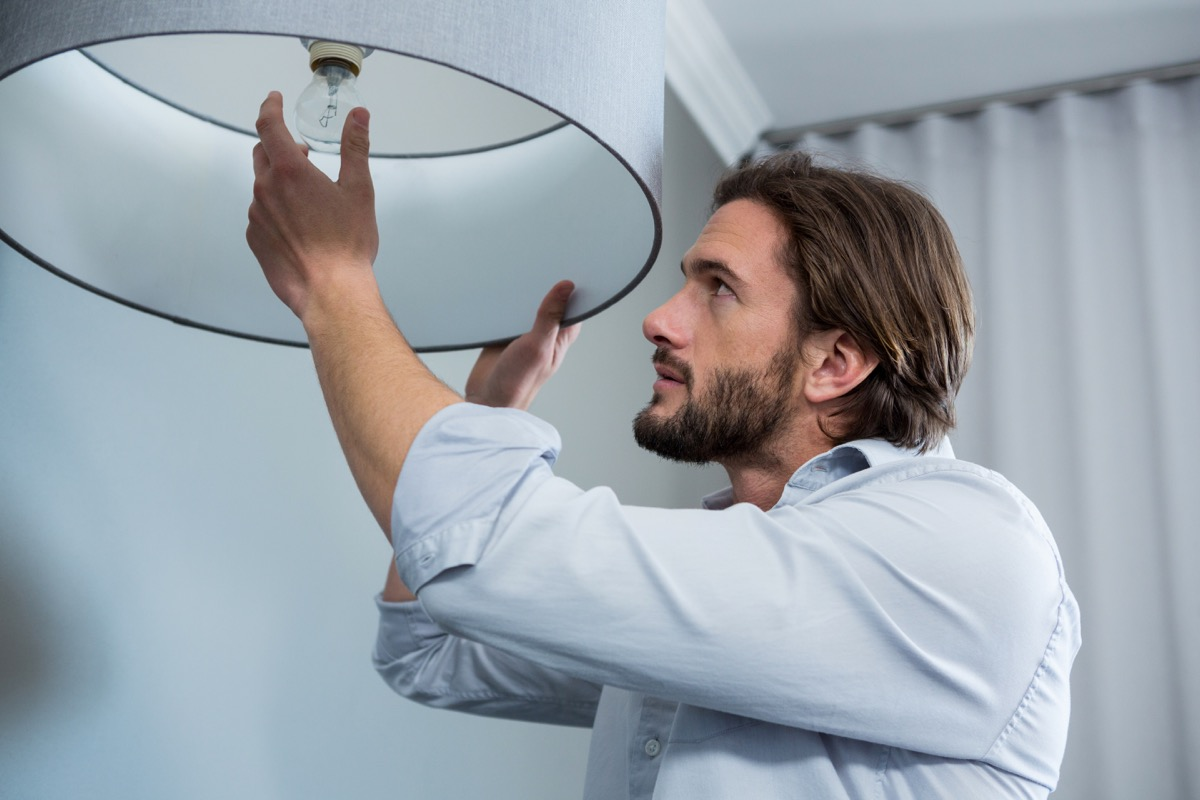Man installing a bulb in living room at home