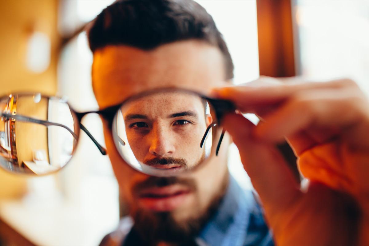 guy is holding his eyeglasses
