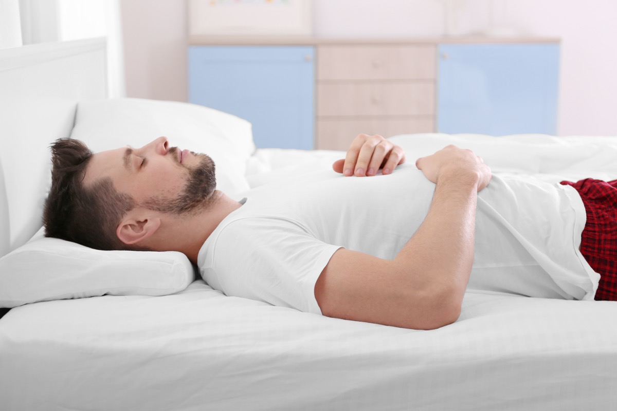 Young man lying on bed with orthopedic pillow at home