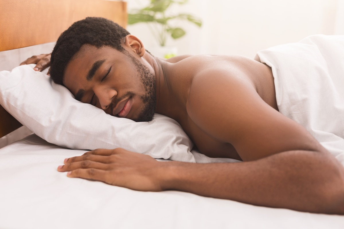 man sleeping naked on stomach in bed at home,