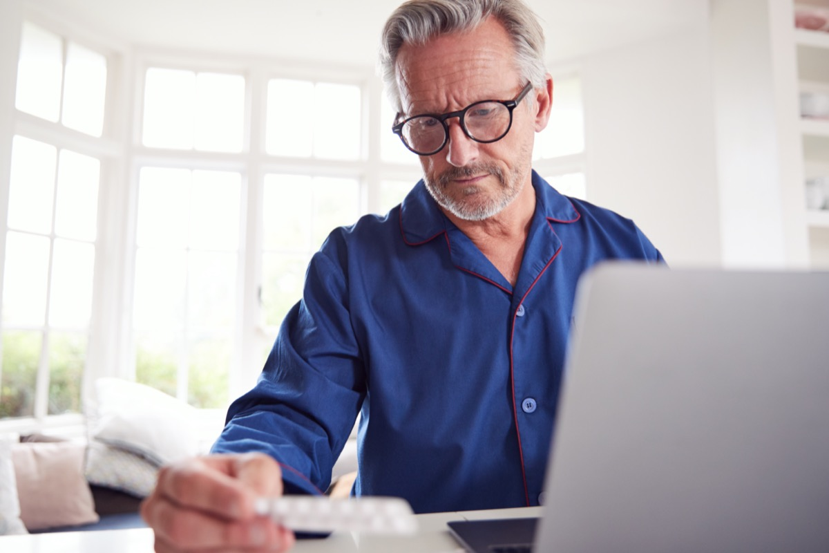 Mature Man At Home Looking Up Information About Medication Online Using Laptop