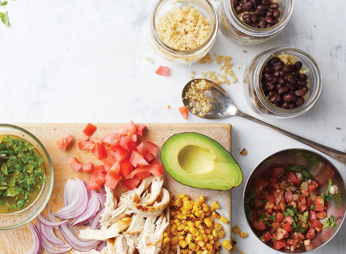 mexican quinoa and chicken salad on wooden cutting board with bowl of salsa