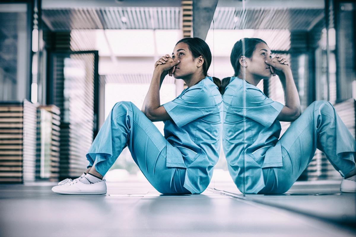 Worried nurse sitting in hospital corridor