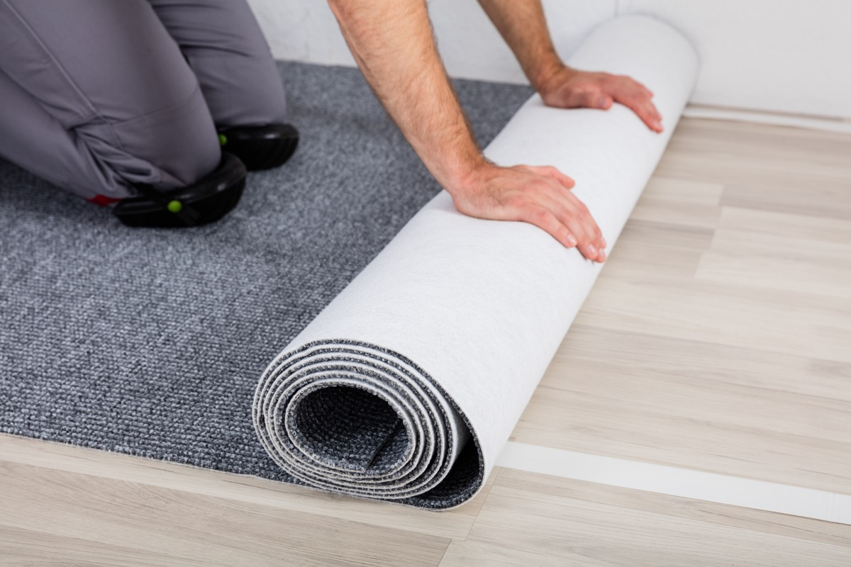 Worker's Hands Unrolling Carpet On Floor At Home