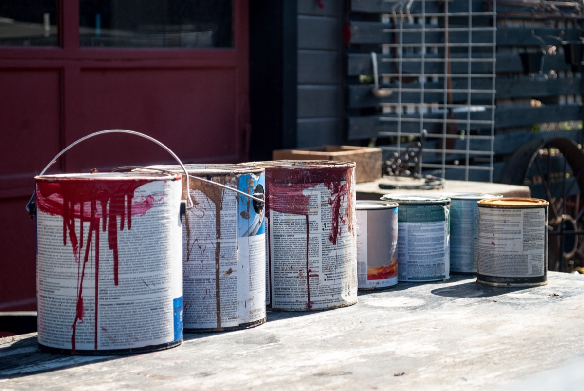 Old paint cans in front of a garage