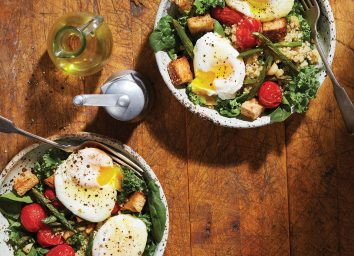 red and green breakfast salad in bowls with eggs and oil