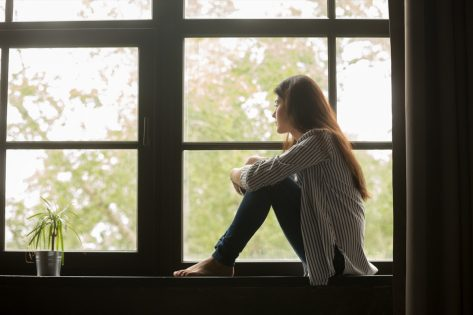 Thoughtful girl sitting on sill embracing knees looking at window, sad depressed teenager spending time alone at home, young upset pensive woman feeling lonely or frustrated thinking about problems