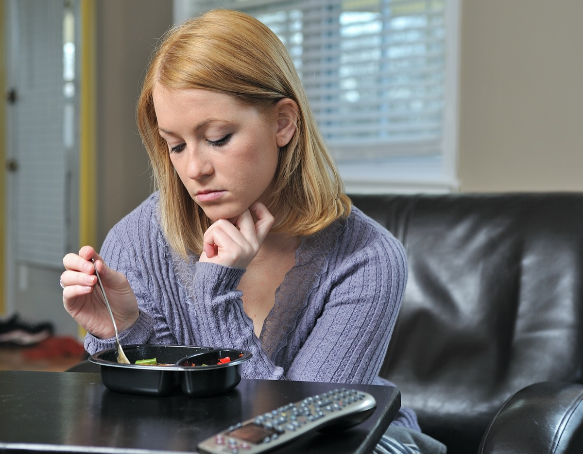 woman sitting in chair in pastel sweater eating a frozen (TV) dinner