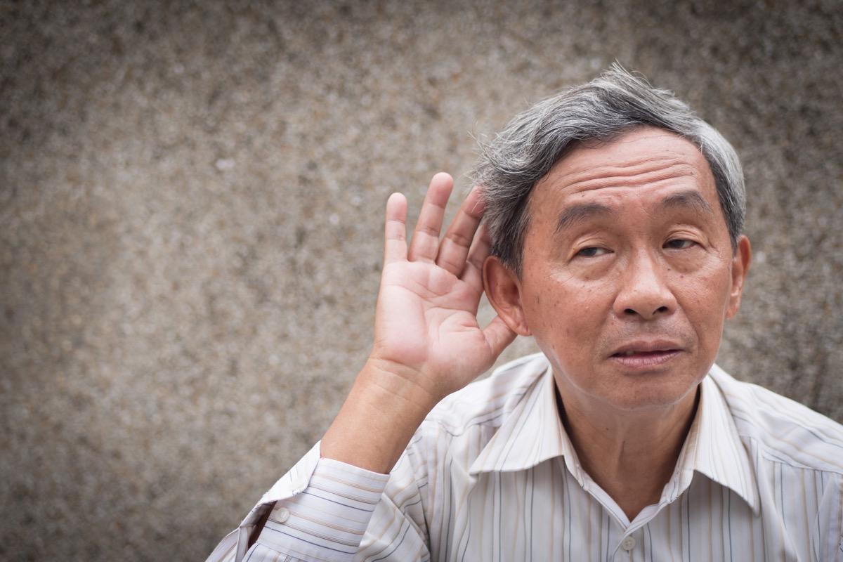 sad senior listening, old man hearing concept of deafness or hard of hearing