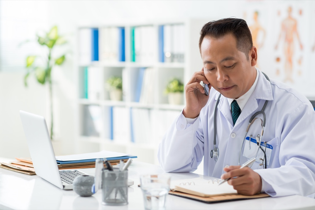 Doctor checking his daily planner when talking to his patient on the phone