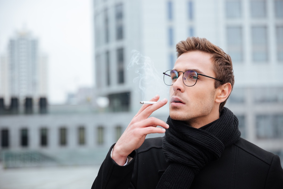 Business man in glasses and warm clothes smoking cigarette on the street