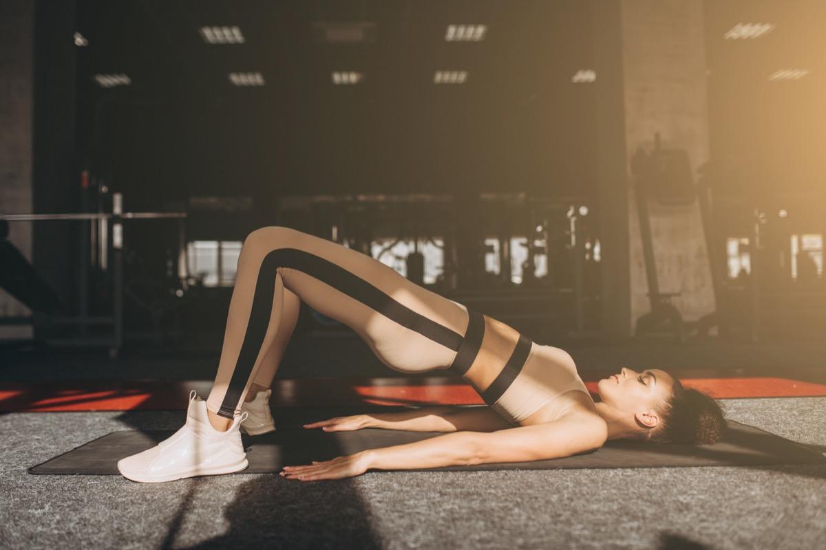 Sporty girl doing floor hip raise or butt lift exercise lying on floor