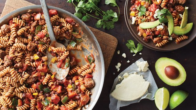 one skillet taco pasta with spoon, cotija cheese, and sliced avocado