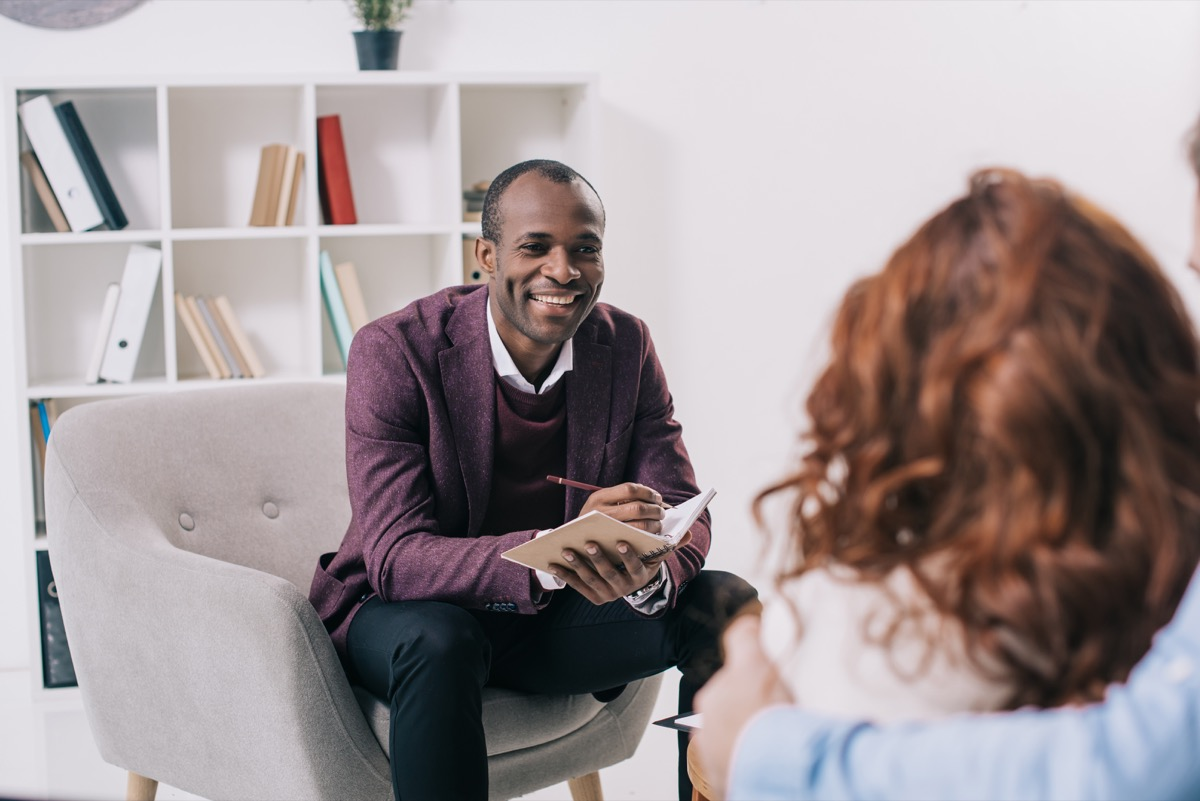 african american psychiatrist talking to young couple