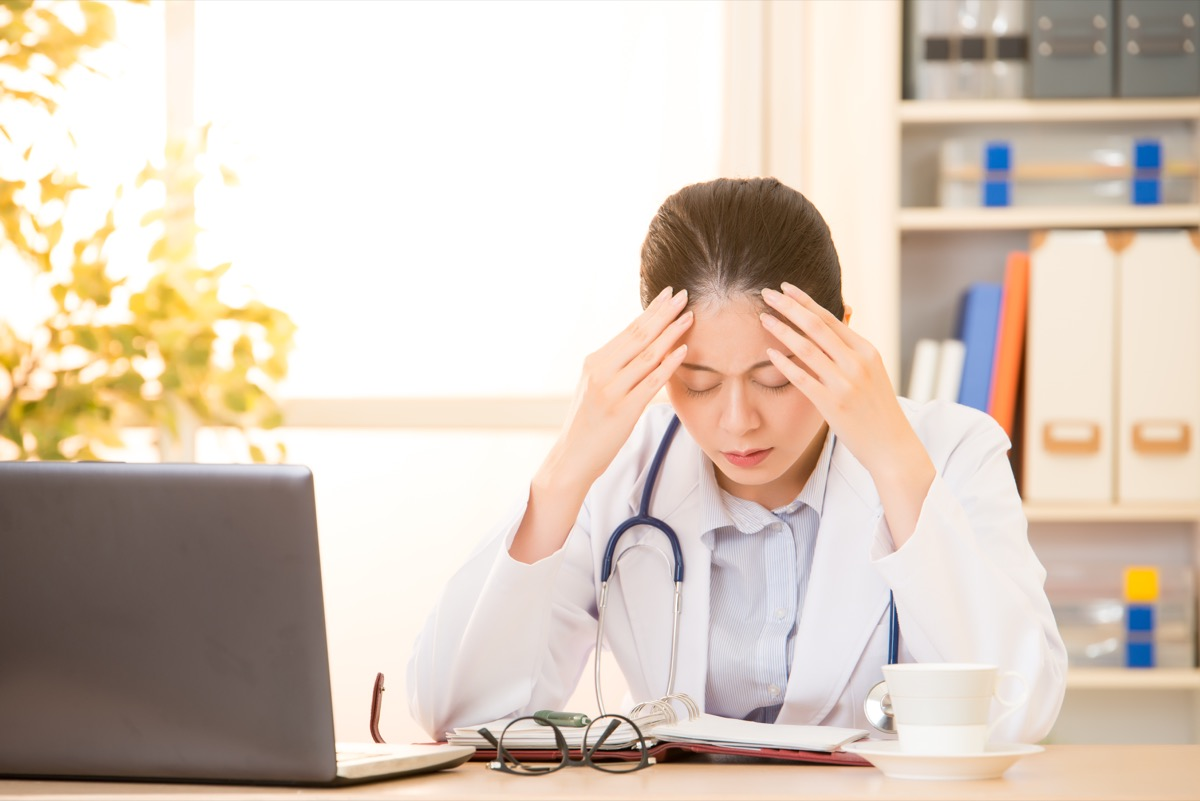 Woman doctor stressed with migraine headache overworked. Health care professional in lab coat wearing stethoscope at hospital