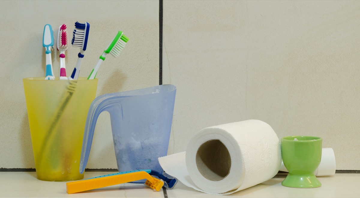 Messy toilet shelf with a blue cup, yellow cup with toothbrushes, toilet paper, green cup and two razors