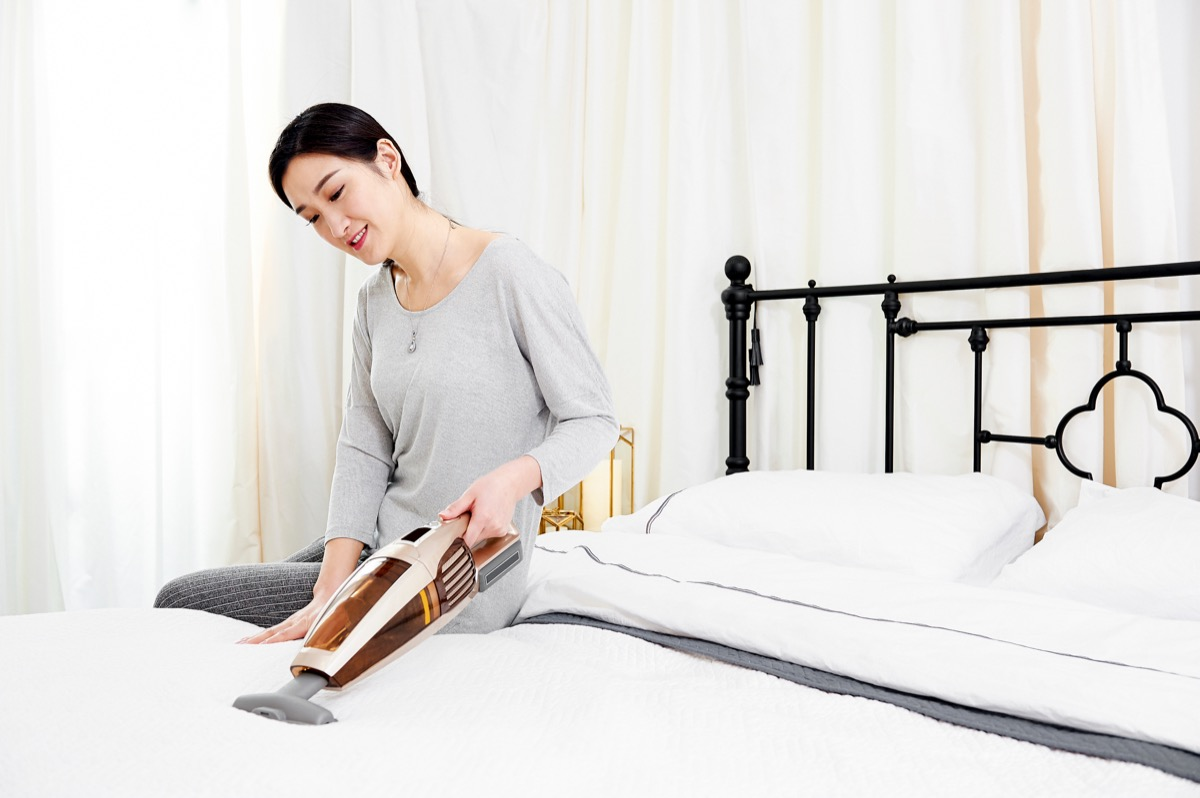 woman sitting in bed using a wireless vacuum cleaner to clean bedding mites