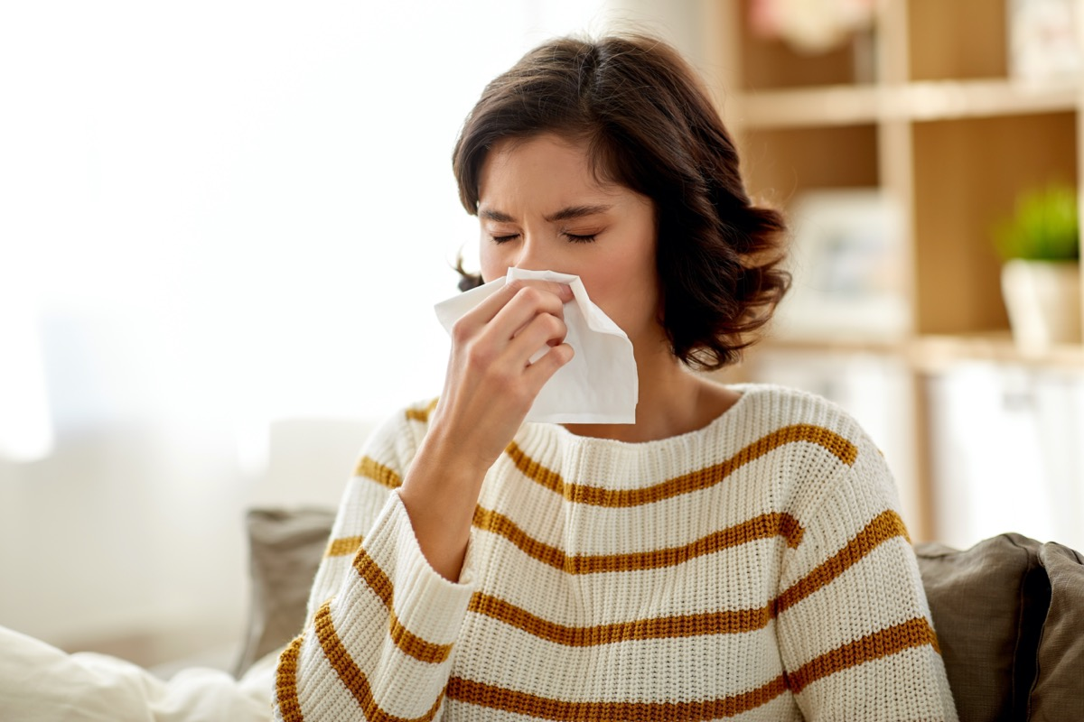 Sick woman blowing her runny nose in paper tissue at home.
