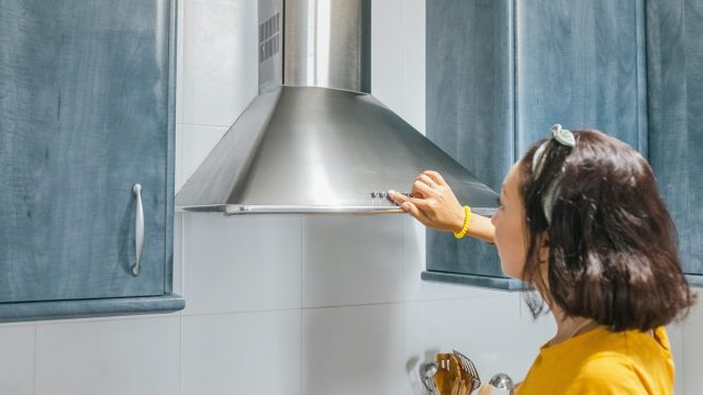 Woman turn on exhaust ventilation in the kitchen