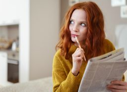 Thoughtful young woman doing a cryptic crossword puzzle in a newspaper