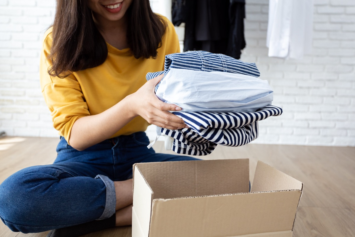 Woman holding Clothes with Donate Box In her room, Donation Concept