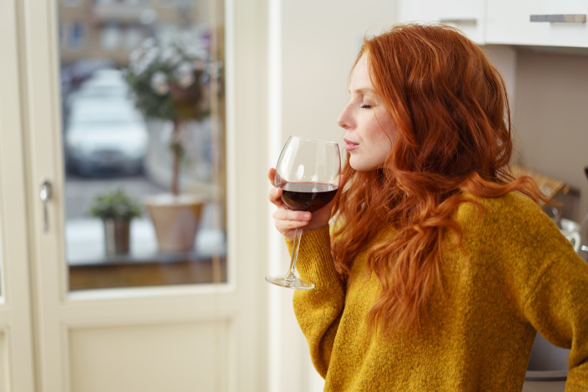 Young redhead woman standing in her apartment sipping a glass of red wine with her eyes closed in pleasure