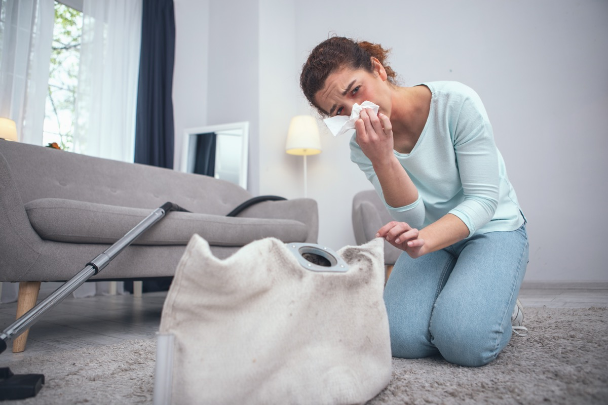 woman being prone to dust allergies suffering from consequences of not wearing any personal protective equipment while cleaning dirty carpet