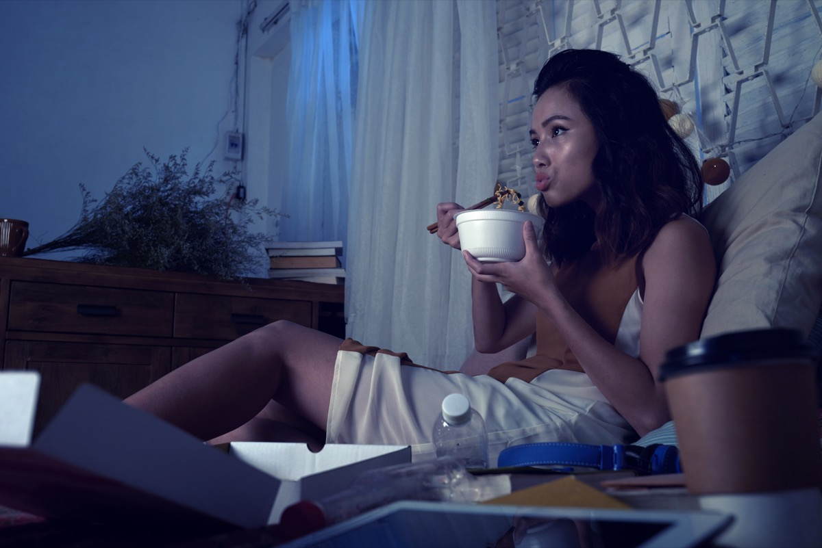 woman eating ramen soup and watching tv series late at night