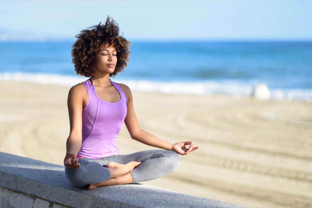 Black woman, afro hairstyle, doing yoga asana in the beach with eyes closed. Young Female wearing sport clothes in lotus pose with defocused background