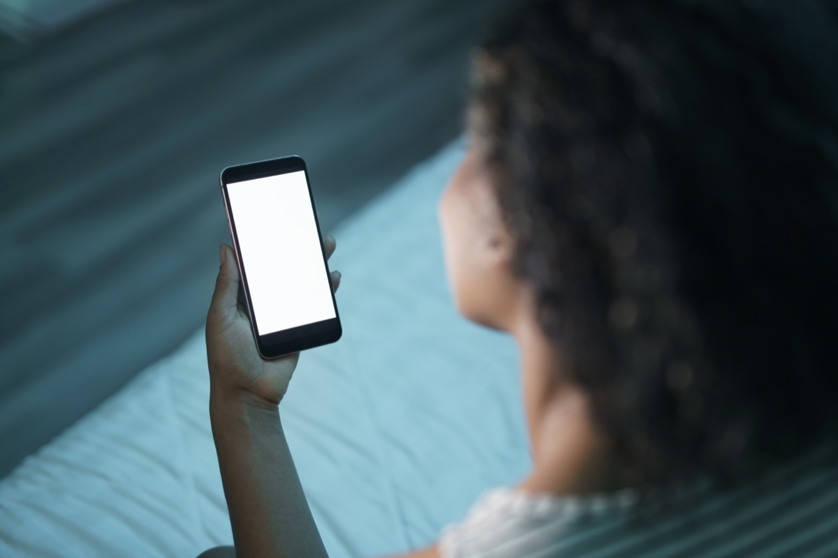 African american woman at home with smartphone