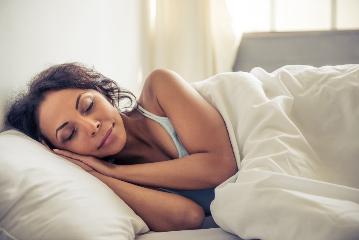 woman smiling while sleeping in her bed at home