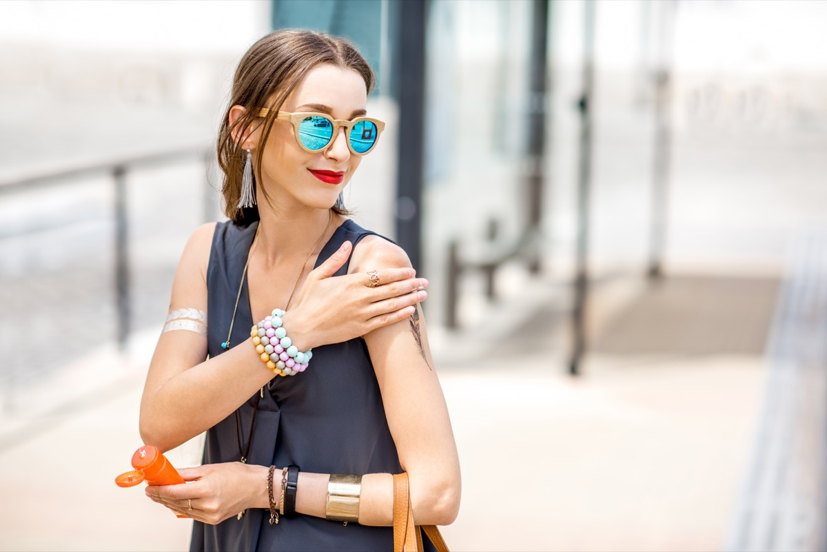 woman applying sunscreen lotion standing outdoors at the urban location during the sunny weather