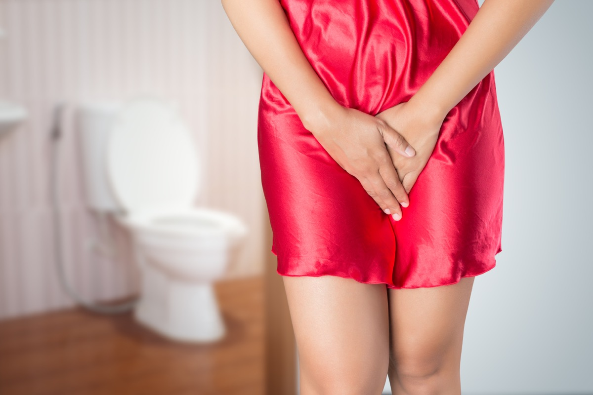 Woman with prostate problem in front of toilet bowl. Lady with hands holding her crotch, People wants to pee - urinary incontinence concept