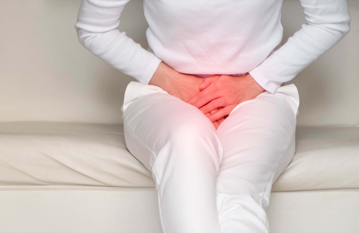 woman with hands holding her crotch in pain. Bladder pain