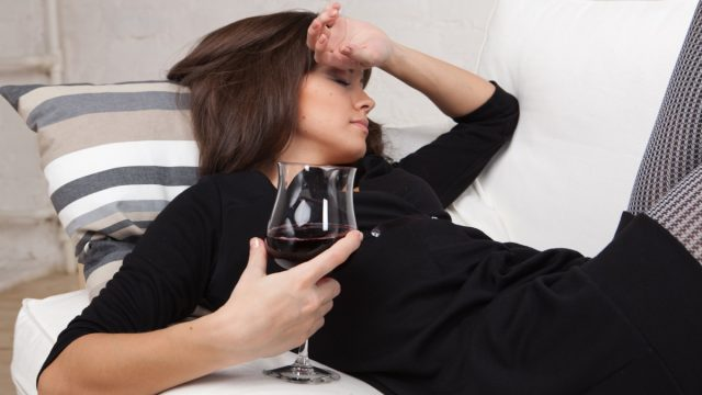 Young woman relaxes at home on the white sofa with a glass of red wine