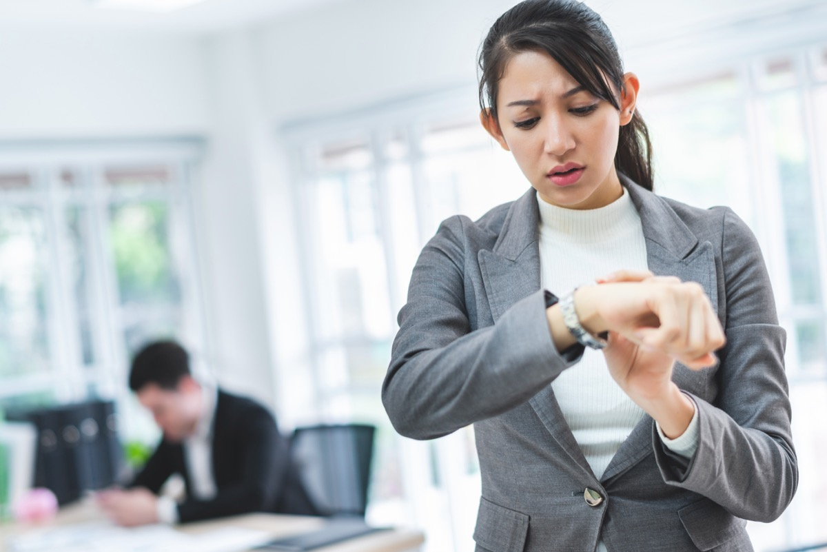 Asian business woman looking at the watch time worried and afraid of getting late to meeting