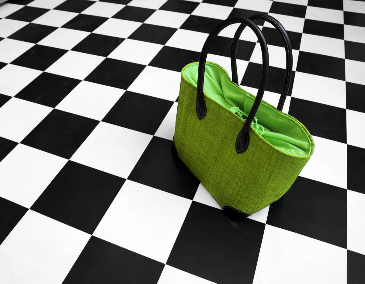 Green purse on black and white floor
