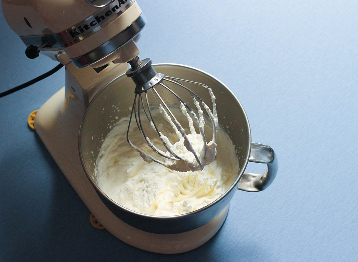 Prepared whipped cream in a stand mixer.
