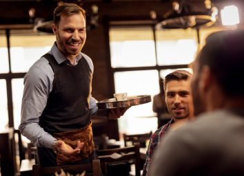 Waiter acting friendly to customers at a restaurant.
