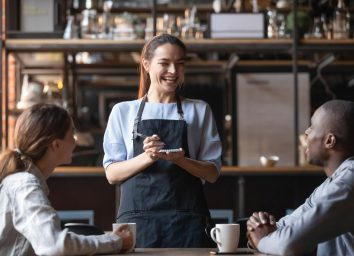 Waitress laughing with customer at a restaurant.