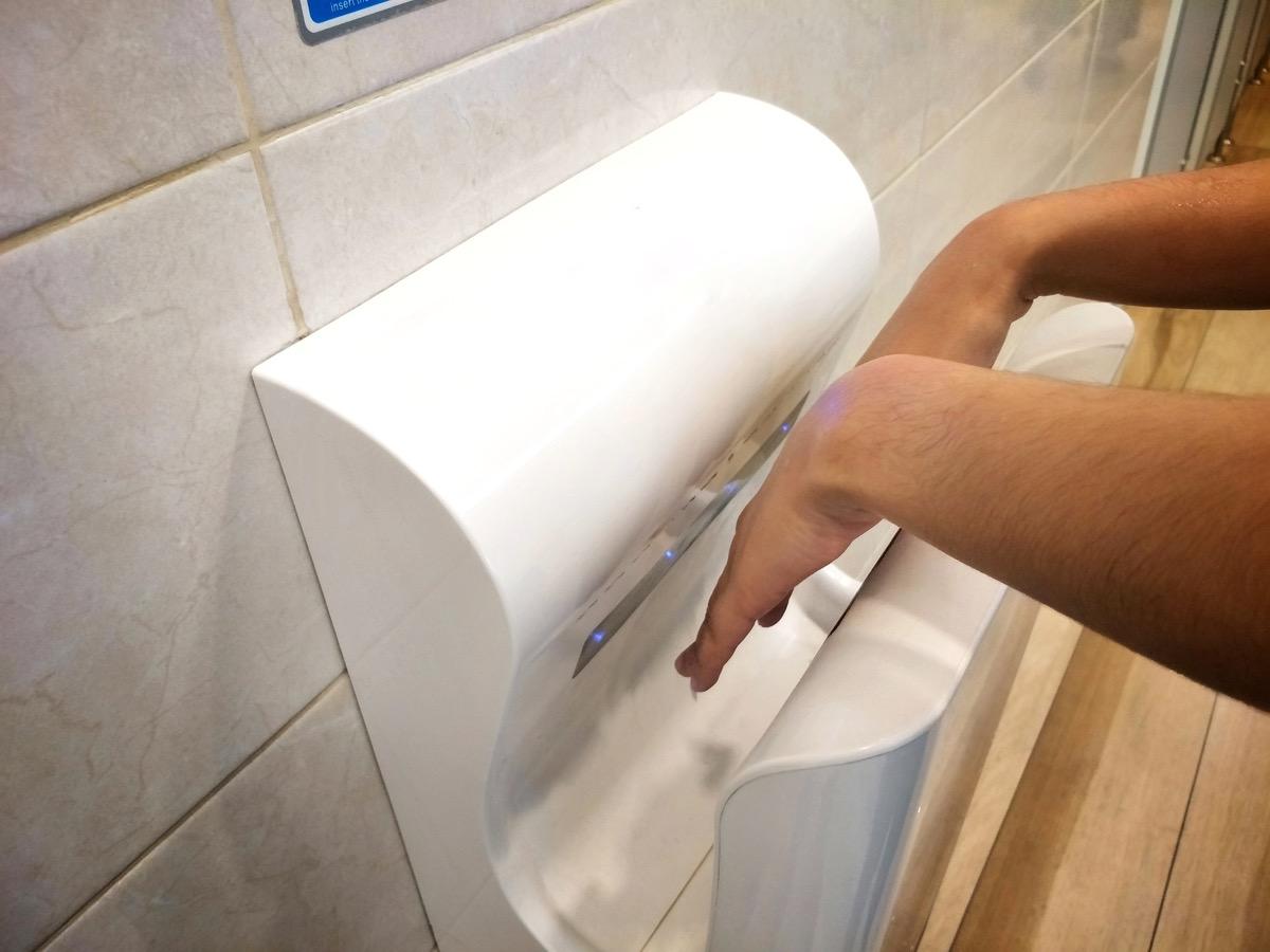 Female dries wet hand in modern vertical hand dryer in public restroom