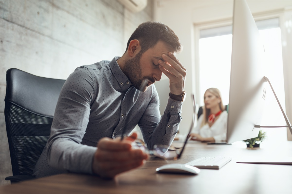 frustrated and stressed businessman sitting at the office front a computer and holding head