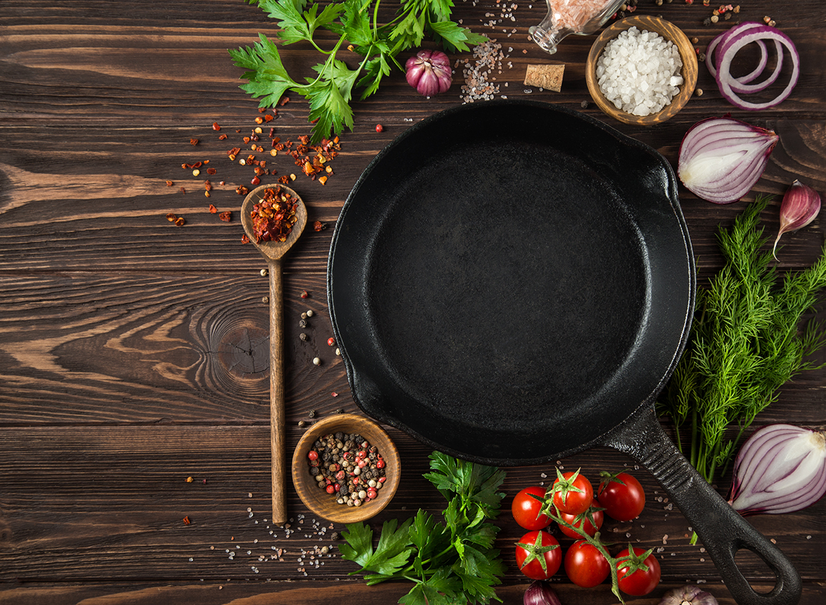 cast iron skillet with vegetables, herbs, and spices