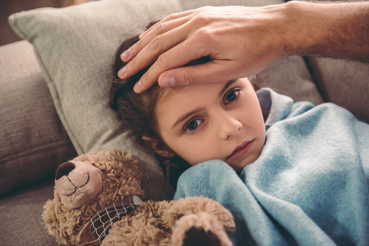 Sick little girl covered in blanket is lying on couch